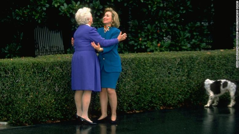 Hillary Rodham Clinton and first lady Barbara Bush exchange hugs as dog Millie sniffs hedge, on the grounds of the White House on November 19, 1992.