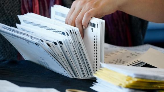 An election worker handles ballots as vote counting in the general election continues at State Farm Arena on Thursday, Nov. 5, 2020, in Atlanta.