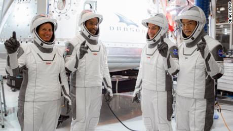 In this Thursday, Sept. 24, 2020, image released by SpaceX/NASA, NASA's SpaceX Crew-1 astronauts, from left, mission specialist Shannon Walker, pilot Victor Glover, and Crew Dragon commander Michael Hopkins, all NASA astronauts, and mission specialist Soichi Noguchi, Japan Aerospace Exploration Agency (JAXA) astronaut, gesture during crew equipment interface testing at SpaceX headquarters in Hawthorne, Calif. SpaceX's second astronaut flight is off until mid-November 2020 because red lacquer dripped into tiny vent holes in two rocket engines that now must be replaced. (SpaceX/NASA via AP)