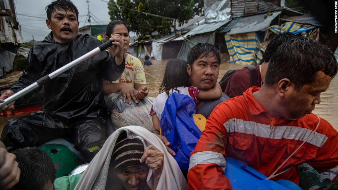 People ride to safety in a boat after being rescued from flood waters in Rodriguez, Philippines, on Thursday, November 12.