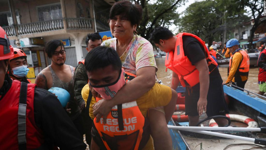A rescuer carries a woman out of a boat in Marikina, Philippines, on November 12.