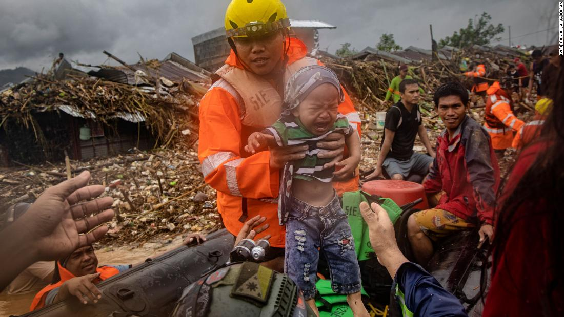 A rescuer carries a child in Rodriguez, Philippines, on November 12.