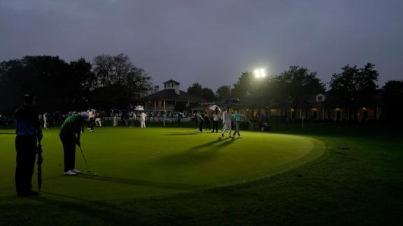 Golfers practice on the putting green next near the Augusta National Golf Course clubhouse before the start of the first round in near darkness.