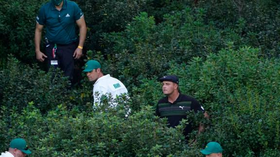 Bryson DeChambeau is aided by caddies and officials to look for his ball in the bushes on the 13th hole after a wayward shot.