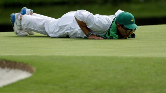 Kessler Karain, caddie for Patrick Reed, lines up a putt for the American.