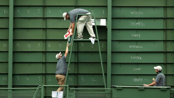 Course workers fill the scoreboard on the 15th hole during the first round.