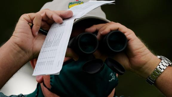 A course worker watches play on the 17th hole during the first round of the Masters golf tournament.