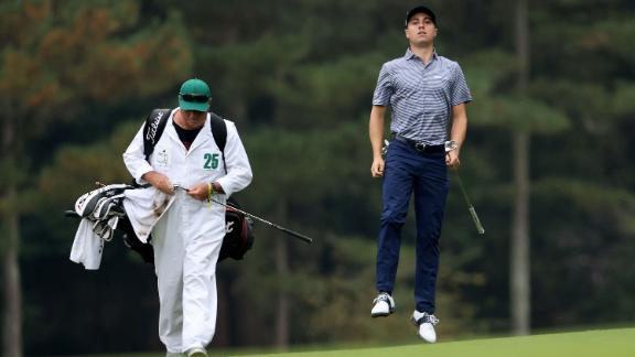 Justin Thomas of the United States jumps to check his lie on the 14th hole on his way to a 69 with four finishing birdies to share the clubhouse lead.