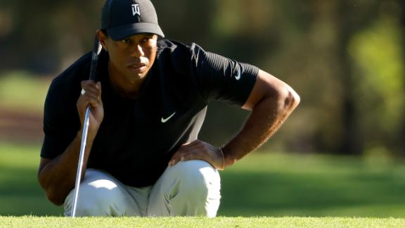 Tiger Woods of the United States lines up a putt on the third green, which he three-putted for a bogey.