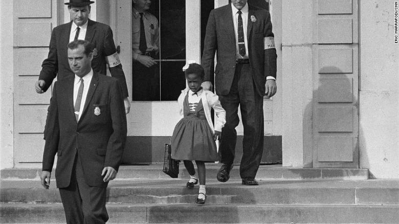 US deputy marshals escort 6-year-old Ruby Bridges from William Frantz Elementary School in New Orleans.
