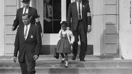 US deputy marshals escort 6-year-old Ruby Bridges from William Frantz Elementary School in New Orleans.