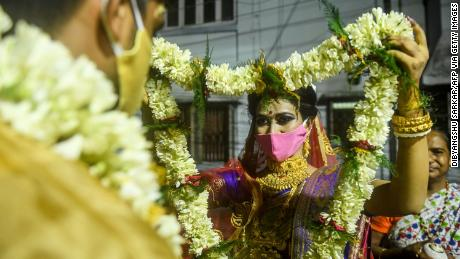 A bride exchanges flower garlands with a groom as part of their traditional marriage ceremony in Kolkata in July, 2020.