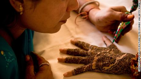 An artist applies henna to the hands of a young Indian bride.
