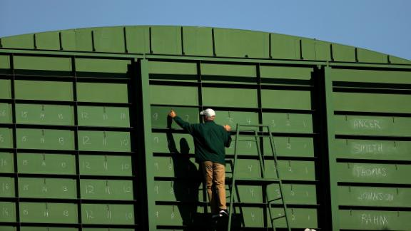 A course worker updates the scoreboard on the eighth green during the third round.