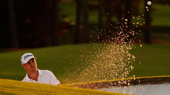Justin Thomas watches his shot out of a bunker on the 18th hole which he eventually bogeyed to fall six behind Johnson.