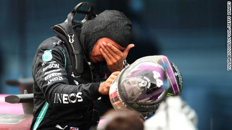 An emotional Hamilton celebrates with his Mercedes team after the race.
