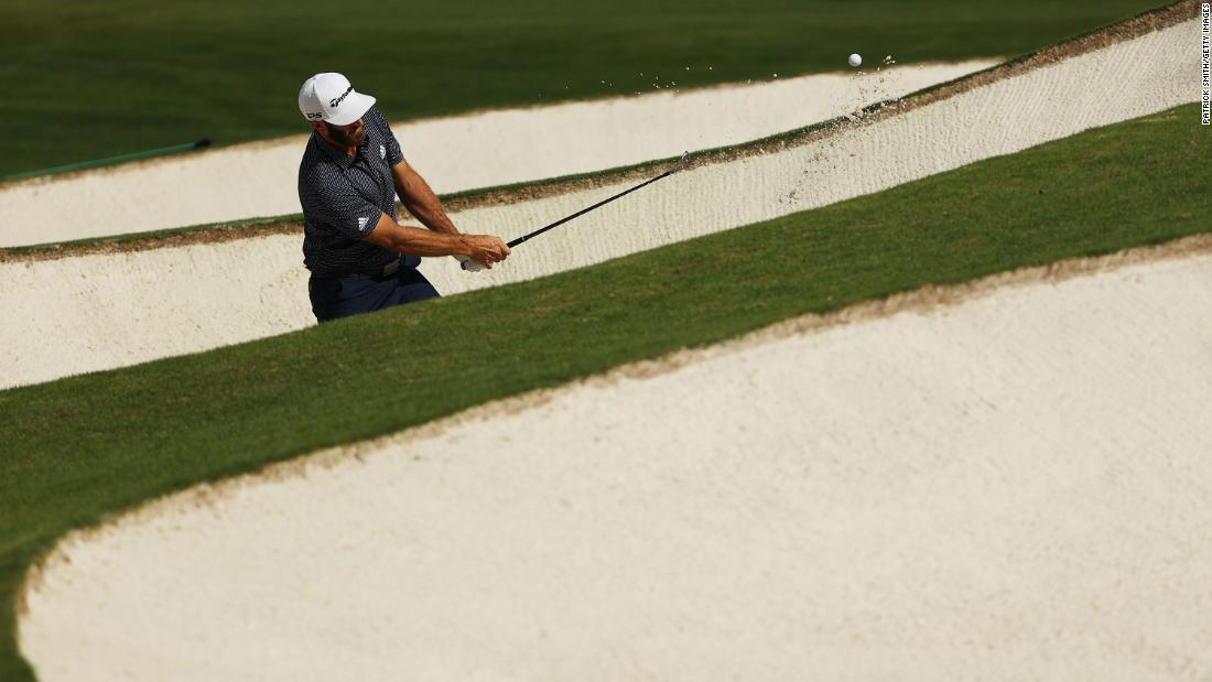 Dustin Johnson of the United States plays a shot from a bunker on the seventh hole.