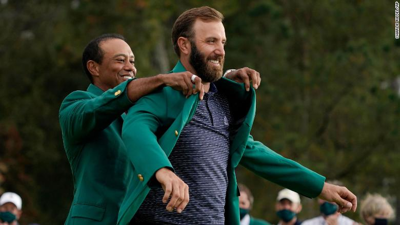 Tiger Woods helps Masters' champion Dustin Johnson with his green jacket after his victory at the Masters golf tournament Sunday, Nov. 15, 2020, in Augusta, Ga.