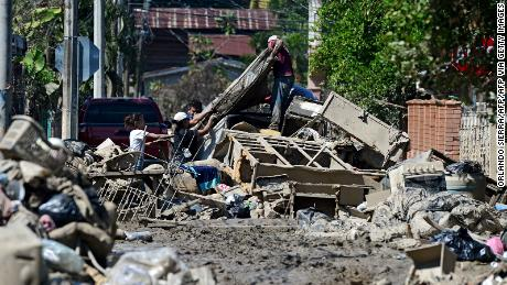 People try to recover belongings amid mud after the passage of Hurricane Eta as they prepare to evacuate the Omonita neighborhood in El Progreso, Yoro department, Honduras.