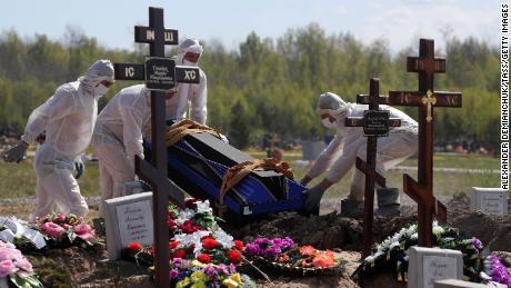Workers wear protective equipment in Novoye Kolpinskoye Cemetery, Saint Petersburg, during a funeral in May.