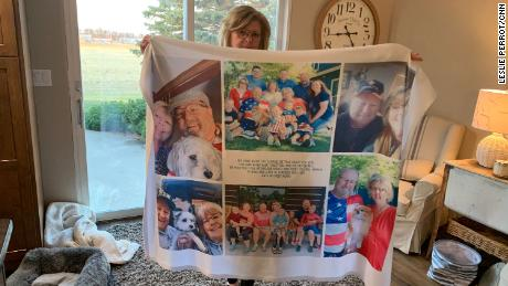 Chris Bjorkman holds up a quilt with photos of her late husband.