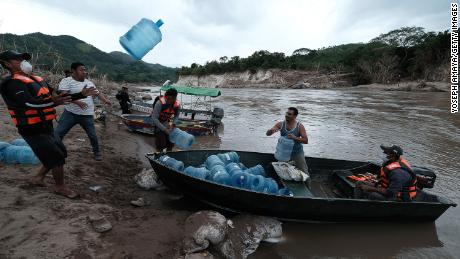 People from San Rafael colony in Honduras prepare for the water shortage as they cross the Ulua River to evacuate Monday.