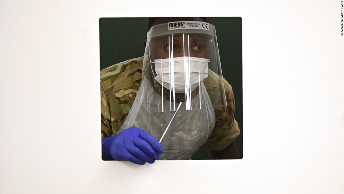 A soldier wearing full PPE waits at a window for a colleague's swab as they practice for the arrival of members of the public inside a rapid testing center at a tennis center in Liverpool on November 6.