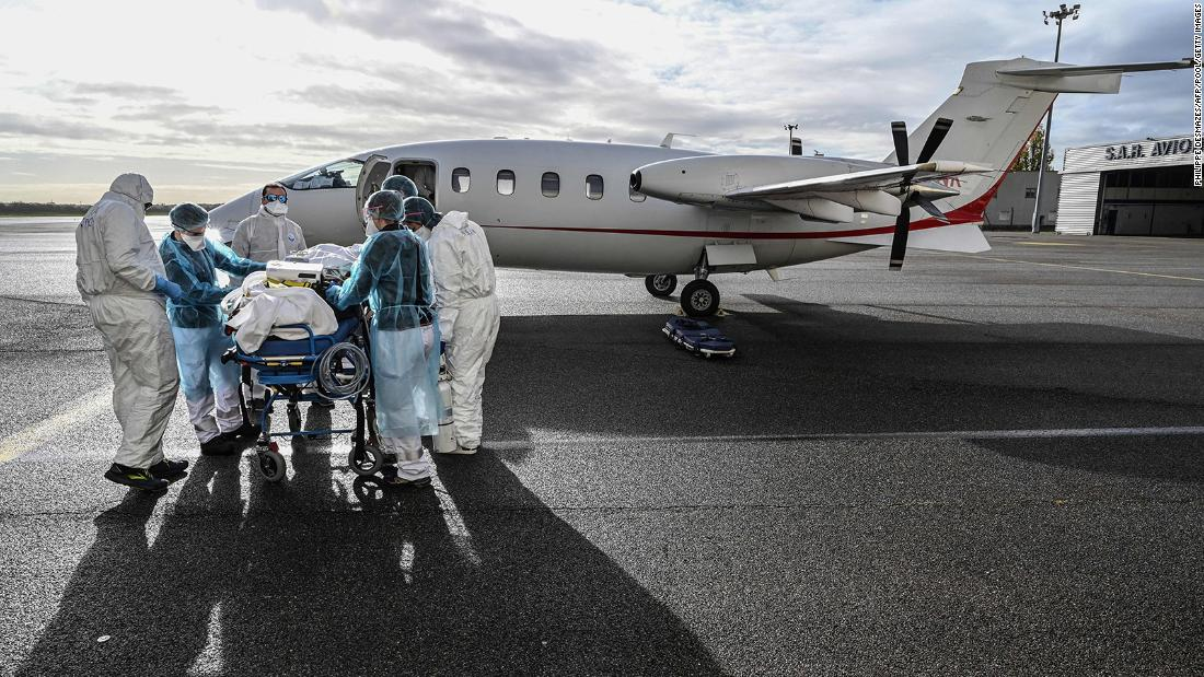 Medical staff transport a patient to a waiting medical flight, to be evacuated to another hospital, at the Lyon-Bron Airport in France on Monday, November 16.