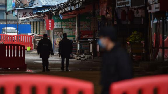 Security guards patrol outside the Huanan Seafood Wholesale Market where the coronavirus was detected in Wuhan on January 24, 2020 - The death toll in China's viral outbreak has risen to 25, with the number of confirmed cases also leaping to 830, the national health commission said. (Photo by Hector RETAMAL / AFP) (Photo by HECTOR RETAMAL/AFP via Getty Images)