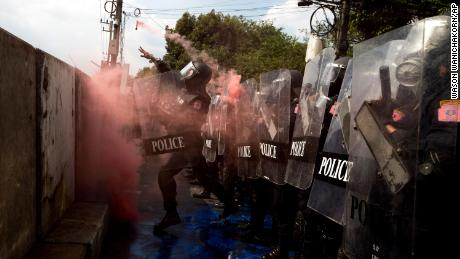 Riot police throw a smoke bomb back to pro-democracy protesters near the parliament in Bangkok, on November 17, 2020.