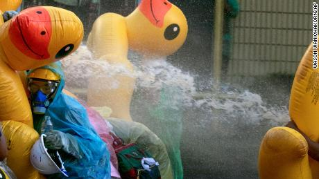 Pro-democracy protesters take cover with inflatable ducks as police fire water cannons during an anti-government rally near the Parliament in Bangkok, on November 17, 2020.