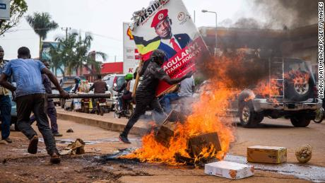 A supporter of Bobi Wine carries his poster as they protest against his arrest in Kampala, Uganda, on November 18, 2020.
