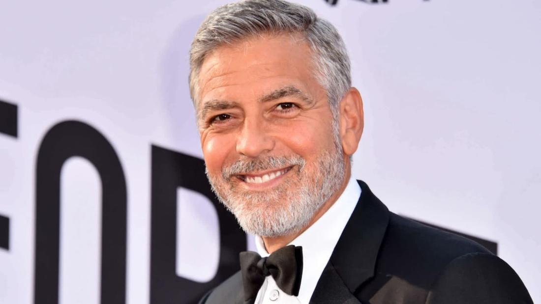 George Clooney cuts his own hair with a device attached to a vacuum cleaner