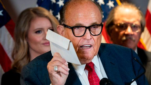 WASHINGTON, DC - NOVEMBER 19: Rudy Giuliani holds up a mail-in ballot as he speaks to the press about various lawsuits related to the 2020 election,  inside the Republican National Committee headquarters on November 19, 2020 in Washington, DC. President Donald Trump, who has not been seen publicly in several days, continues to push baseless claims about election fraud and dispute the results of the 2020 United States presidential election. (Photo by Drew Angerer/Getty Images)