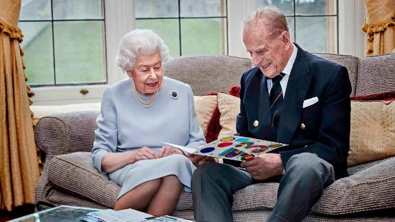 The Queen and Prince Philip look at a homemade anniversary card that was given to them by their great-grandchildren Prince George, Princess Charlotte and Prince Louis in November 2020.
