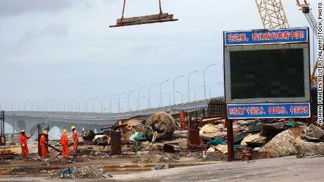 """A signboard at the construction site of the China-Maldives Friendship Bridge reads: """"Here, we represent China!"""""""