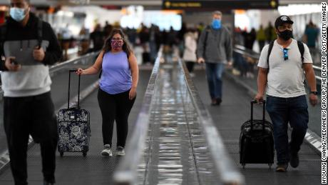 Traveling at Denver International Airport on Friday.  More than 1 million people were checked by the TSA at U.S. airports on Friday, despite warnings urging people not to travel due to the growing Covid-19 cases.