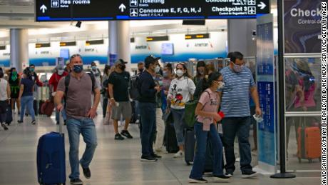 Travelers wearing protective face masks walking through Miami International Airport on Sunday.