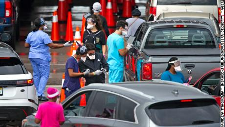 Vehicles line up as a health care workers help to check in people being tested at the COVID-19 drive-thru testing center at Hard Rock Stadium in Miami Gardens, Florida on Sunday, Nov. 22, 2020. (David Santiago/Miami Herald/Tribune News Service via Getty Images)