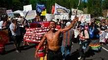 Activists and tribal citizens block the road to Mount Rushmore National Monument during a protest on July 3, 2020.
