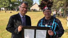 Thomas Kemper, the former general secretary of global ministries for the United Methodist Church, and Wyandotte Nation Chief Billy Friend hold a deed signifying the transfer of land to the tribe.