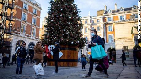 Pedestrians walk past a Christmas tree in Covent Garden in central London, on November 22, 2020.