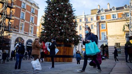 "Pedestrians wearing a protective face covering to combat the spread of the coronavirus, walk past a Christmas tree in Covent Garden in central London, on November 22, 2020, as the four-week national shutdown imposed in England continues, forcing people to stay home and businesses to close owing to a second wave of the Covid-19 pandemic. - British Prime Minister Boris Johnson will confirm that coronavirus lockdown restrictions across England are to end on December 2, his office said Saturday. The lockdown will be followed by a return to a three-tiered set of regional restrictions as part of the government's ""COVID Winter Plan"", it added in a statement. (Photo by Tolga Akmen / AFP) (Photo by TOLGA AKMEN/AFP via Getty Images)"