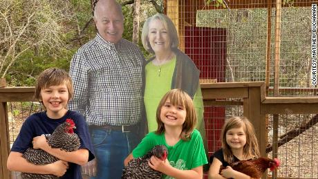 Quinton, Oliver and Clara Buchanan (l-r) have enjoyed posing for photos with the cutout of their grandparents.