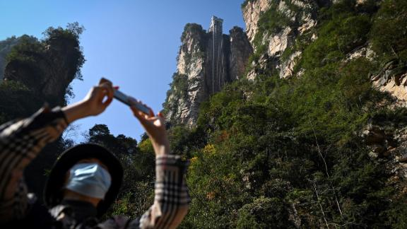 This picture taken on November 13, 2020 shows a tourist with a face mask using her mobil phone to take a picture at the entrance of the Bailong elevators in Zhangjiajie, China