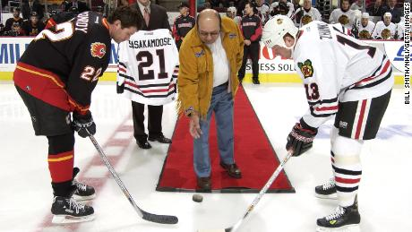Craig Conroy #22 of the Calgary Flames and Alexei Zhamnov #13 of the Chicago Blackhawks pose for the ceremonial face off being dropped by Fred Sasakamoose at the United Center on October 19, 2002.