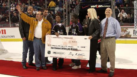 Fred Sasakamoose reacts as he is presented with a check for Johnny's Jems and Jets Hockey team during a ceremony celebrating at the United Center on October 19, 2002 in Chicago, Illinois.
