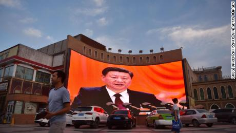 This photo taken on June 4, 2019 shows people walking past a screen displaying images of Chinese President Xi Jinping in Kashgar, western Xinjiang.