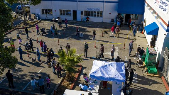 People wait in line to receive food at the Bay Area Rescue Mission's Thanksgiving Giveaway in Richmond, California.
