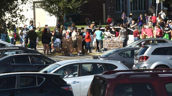 Cars line up at a food distribution site sponsored by local churches and the Second Harvest Food Bank of Central Florida.